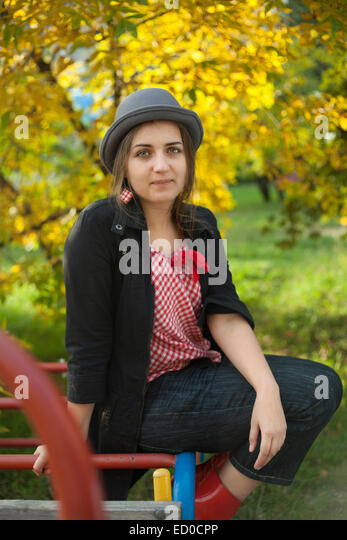 Teenage girl (16-17) with hat relaxing on playground - Stock Image