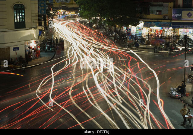 Chaotic traffic is illustrated by the streaking lights in this time exposure of a busy intersection in the Old Quarter, - Stock Image