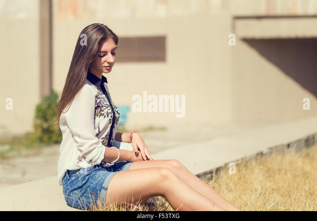 Young hipster girl with long hair sitting on concrete border. Urban portrait of student girl with copy space - Stock Image