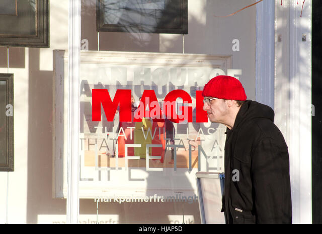 Person in the street passing by bright red MAGIC in shop window - Stock Image