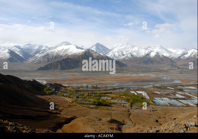 Wide river valley of Lhasa River Kyi Chu with snow covered mountains Tibet China - Stock-Bilder
