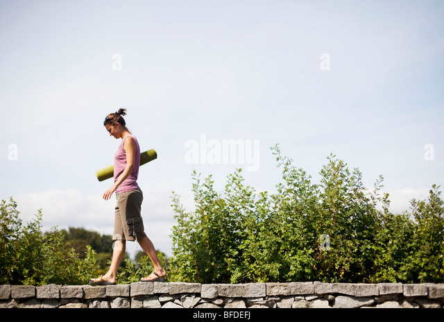 A young woman walks on a stone ledge holding a green yoga mat. - Stock Image