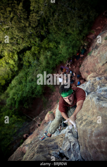 Caucasian male climber reaches out to a final hold high above the jungle in Thailand. - Stock Image
