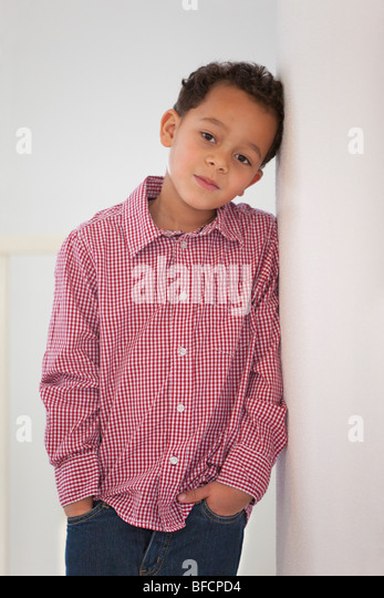 Portrait of a timid seven year old boy - Stock Image