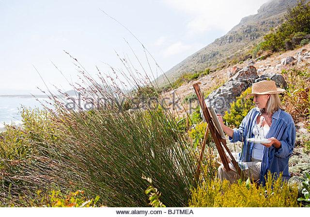 Artist painting on hillside - Stock Image