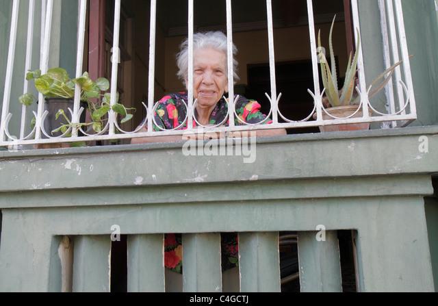 Santo Domingo Dominican Republic Ciudad Colonia Calle Las Mercedes neighbor house window iron fence Hispanic woman - Stock Image