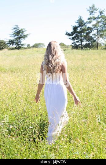 MODEL RELEASED. Young woman in long white dress walking in meadow. - Stock-Bilder