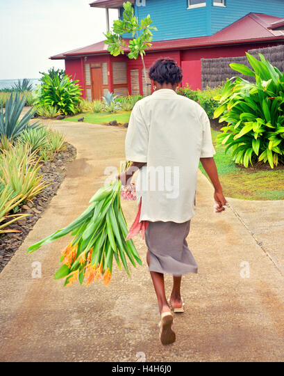 A maid carries flowers to a guest room at  Le Cap Est Lagoon Resort & Spa,Martinique. Caribbean. - Stock Image
