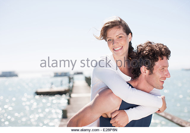 Husband giving wife piggy back ride - Stock Image