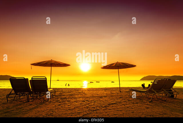 Retro filtered picture of beach chairs and umbrellas on sand at sunset. Concept for rest, relaxation, holidays. - Stock-Bilder
