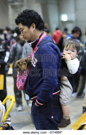 A man carries his baby and pet dog as he visits the 2010 FCI Chiba International Dog Show, near Tokyo, January 24, - Stock-Bilder