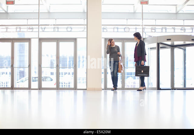 Two businesswomen arriving at conference centre - Stock Image