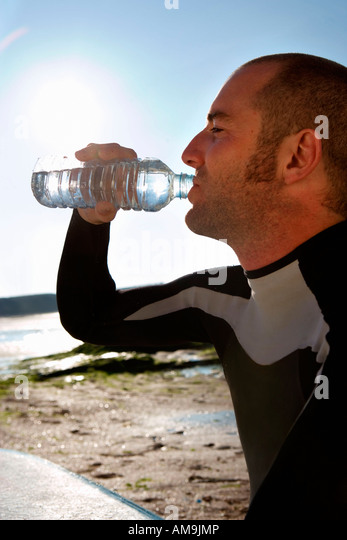 Man sitting with surfboard drinking water . - Stock Image