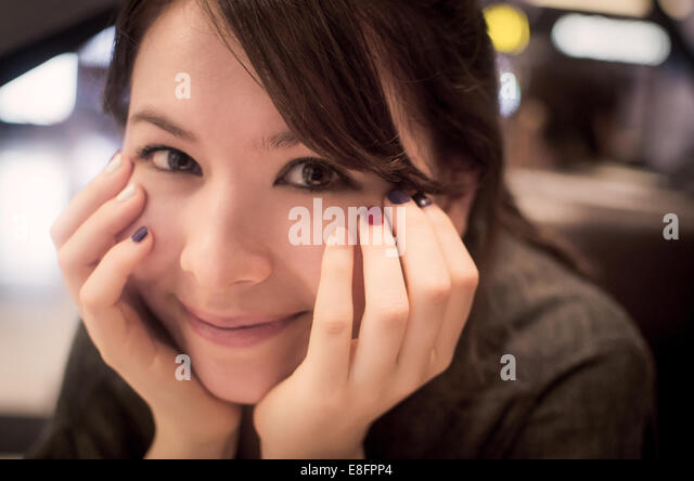 South Korea, Seoul, Portrait of young woman smiling - Stock Image