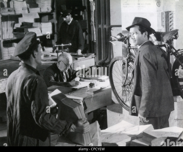 THE BICYCLE THIEF 1948 ENIC film with Lamberto Maggiorani at right as Antonio proudly carrying his new bicycle - Stock Image