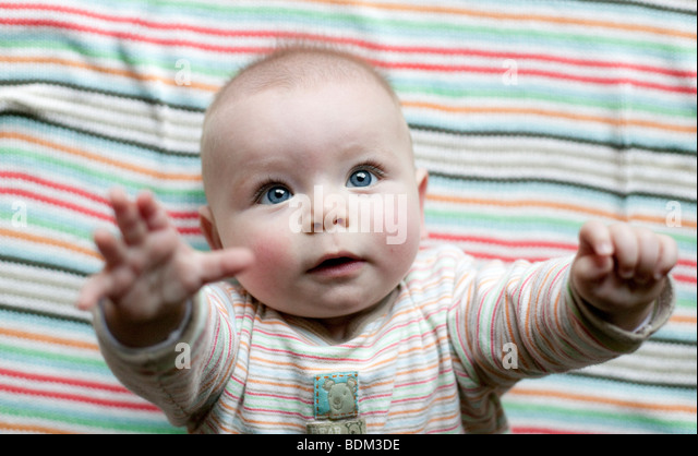 A baby boy lifts his arms to his mother to be picked up. - Stock Image