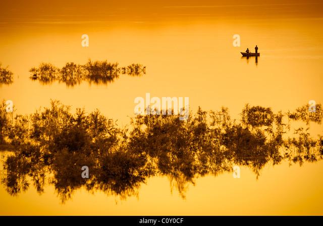 Fishing boat on lake with orange light. - Stock Image