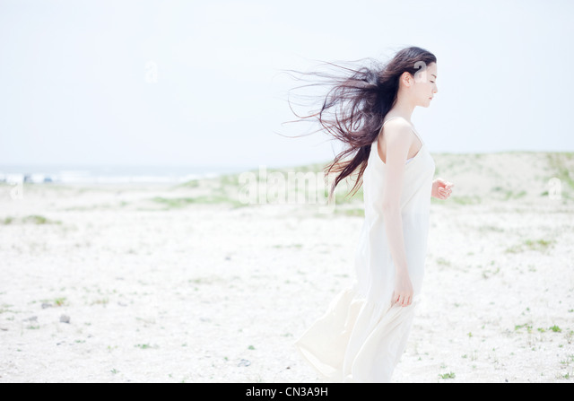 Young woman with long windswept black hair on beach - Stock Image