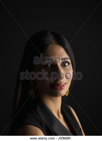 Portrait confident Indian woman with bindi against black background - Stock Image