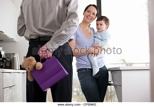 A man returning home to his family after work, holding a gift bag behind his back - Stock Image