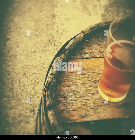 Beer glass on old wooden barrel - Stock-Bilder