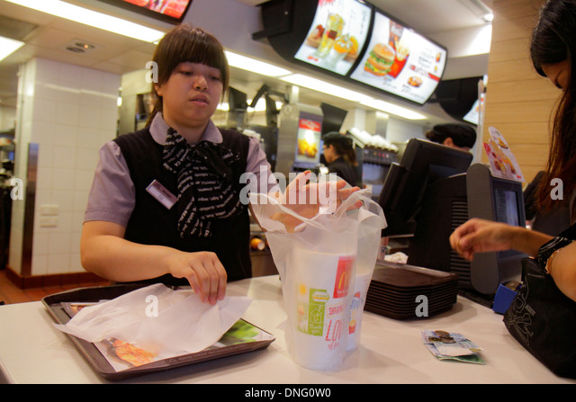 Hong Kong China Kowloon Sham Shui Po McDonald's fast food restaurant counter employee job Asian woman - Stock Image