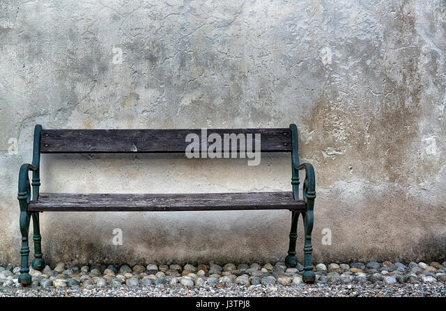 Vintage wooden bench with stone wall in the background - Stock Image