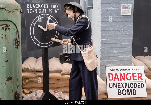 WWII reconstruction of Air Raid Warden setting time for Blackout with unexploded bomb sign nearby - Stock Image
