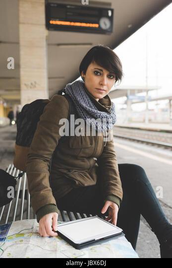 Portrait of female backpacker with map and digital tablet on railway platform - Stock-Bilder