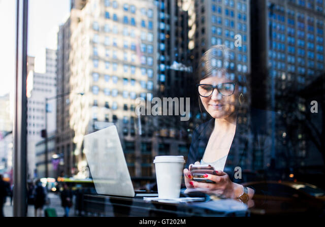 Businesswoman with technologies at cafe seen through window reflecting buildings - Stock-Bilder