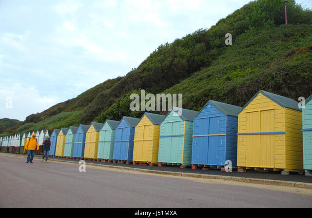 Bournemouth, UK -  13 May: A couple walk by an array of beach huts on the west side of Bournmouth beach. General - Stock Image