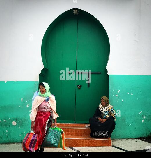 Morrocan women sit in front of a green door in Tangier, Morroco, Africa - Stock Image