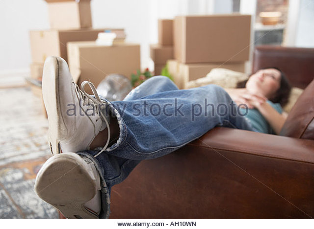Woman lying down on sofa in home with cardboard boxes - Stock Image