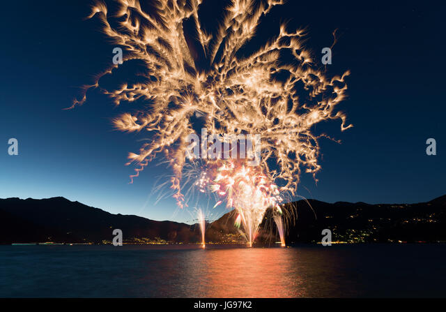 Fireworks on the lakefront of Luino over the Maggiore Lake in a summer evening with blue sky and mountains in the - Stock Image