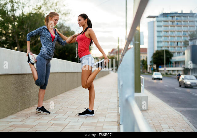Two women stretching feet before jogging - Stock Image