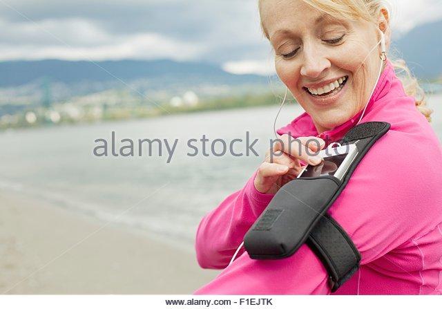 Senior woman adjusting music player while walking. - Stock Image