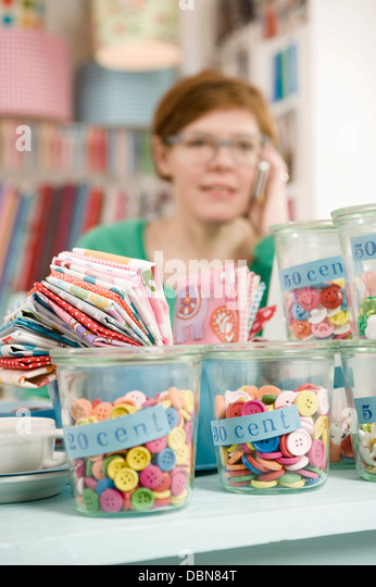 Female Owner of a shop Using Mobile Phone, Munich, Bavaria, Germany, Europe - Stock Image