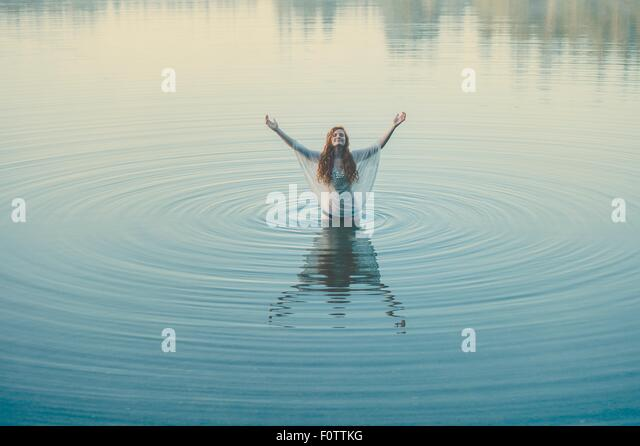Young woman standing in middle of lake ripples with arms open - Stock Image