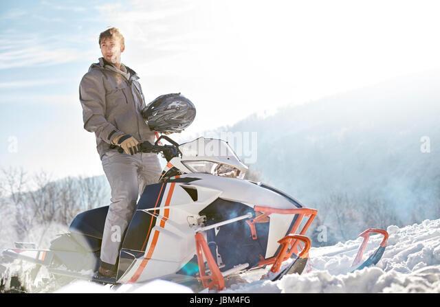 Man riding snowmobile in sunny snowy field - Stock-Bilder