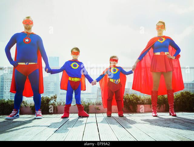 Superhero family holding hands on city rooftop - Stock-Bilder