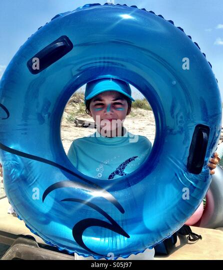 A cute kid in a hat holds up a blue innertube around her sunscreened-face. - Stock Image