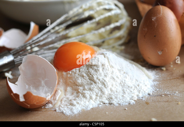Bake situation: Egg yolk on flour with eggshell and whisk - Stock Image