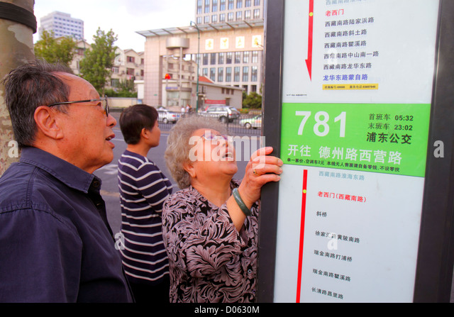 Shanghai China Huangpu District Fuxing East Road bus stop sign route information Asian man woman couple senior reading - Stock Image