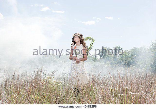 Girl dressed as fairy in field with flower - Stock Image