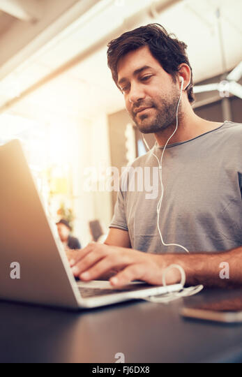 Portrait of young man looking busy working on laptop at a cafe. Caucasian man sitting in coffee shop using laptop. - Stock Image
