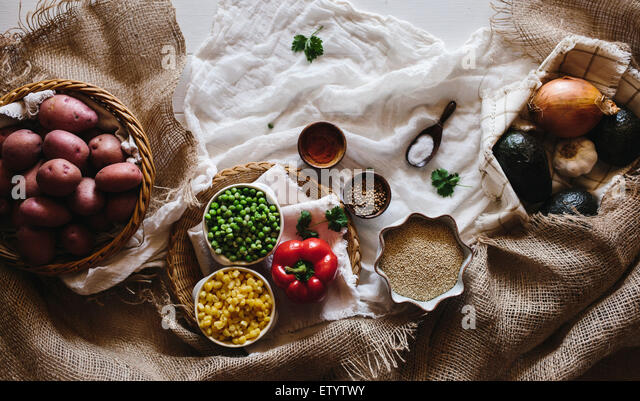 Various Vegetables, including red potatoes, spring peas, corn, avocados, onions, and garlic are displayed on a white - Stock Image