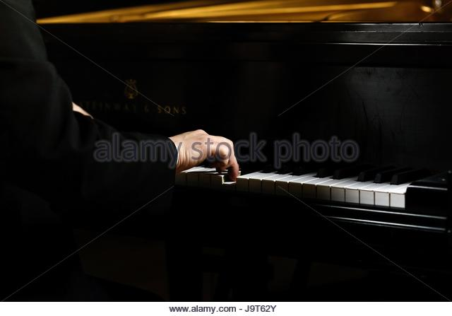 Hands playing a grand piano - Stock Image
