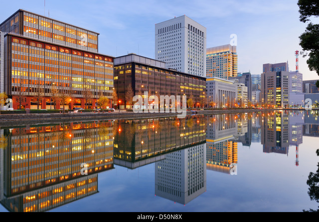 Landmark buildings reflect off the Imperial Palace moat in the Marunouchi district of Tokyo, Japan. - Stock-Bilder