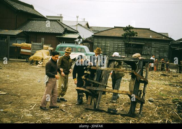 A group of men hold and examine a large piece of wooden and metal equipment on a construction site in Japan, 1952. - Stock Image