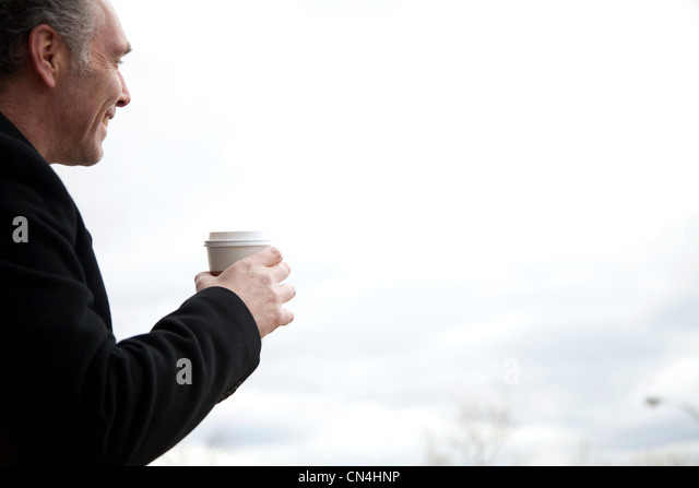 Mature man drinking coffee outdoors - Stock Image